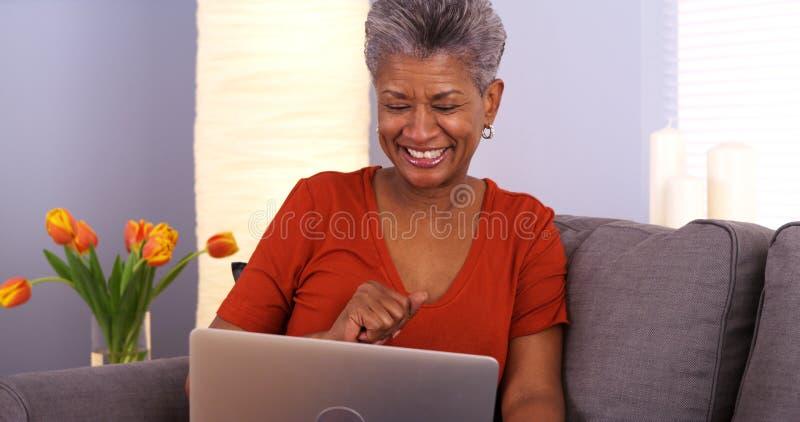 Ältere Afrikanerin, die Spaß mit Laptop hat lizenzfreie stockbilder