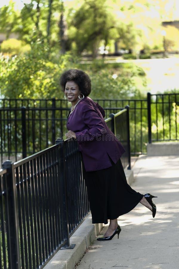 Ältere Afroamerikaner-Frau, die im Rock und im purpurroten Mantel steht stockfotos