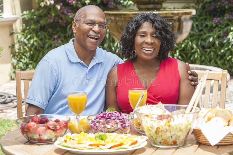 Ältere Afroamerikaner-Paare, die draußen essen lizenzfreies stockbild
