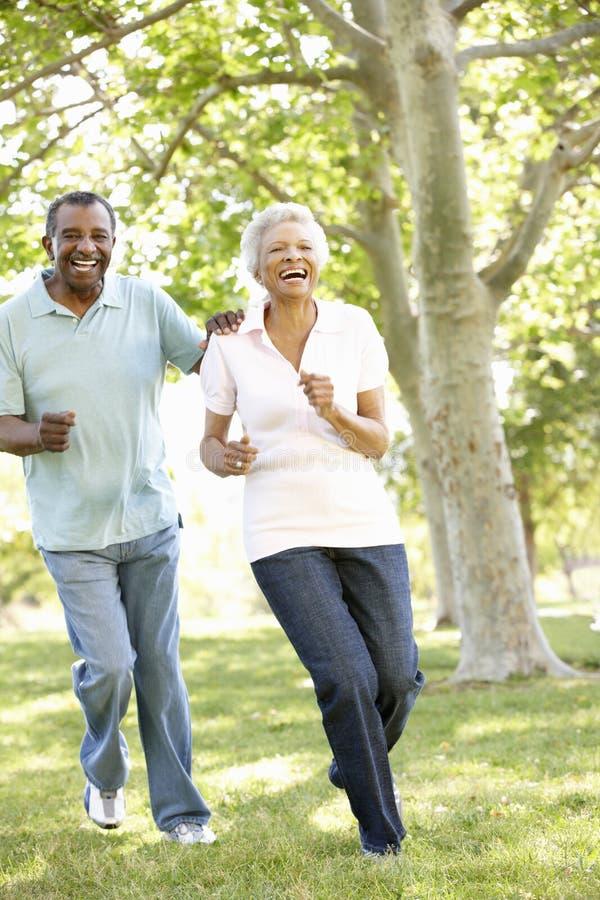 Ältere Afroamerikaner-Paare, die in Park laufen stockbild
