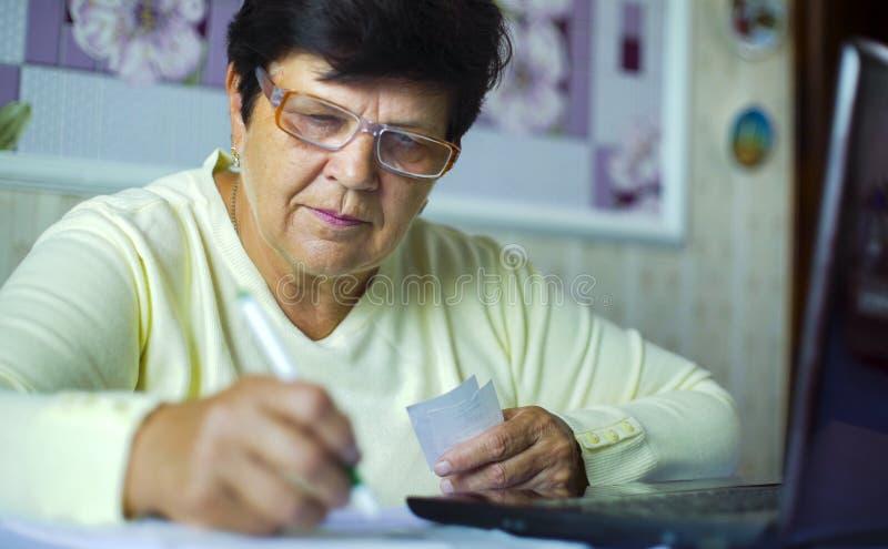 Ältere alte Frau in den Brillen Kosten der täglichen Ausgaben auf Laptop zu Hause überprüfend stockfotos