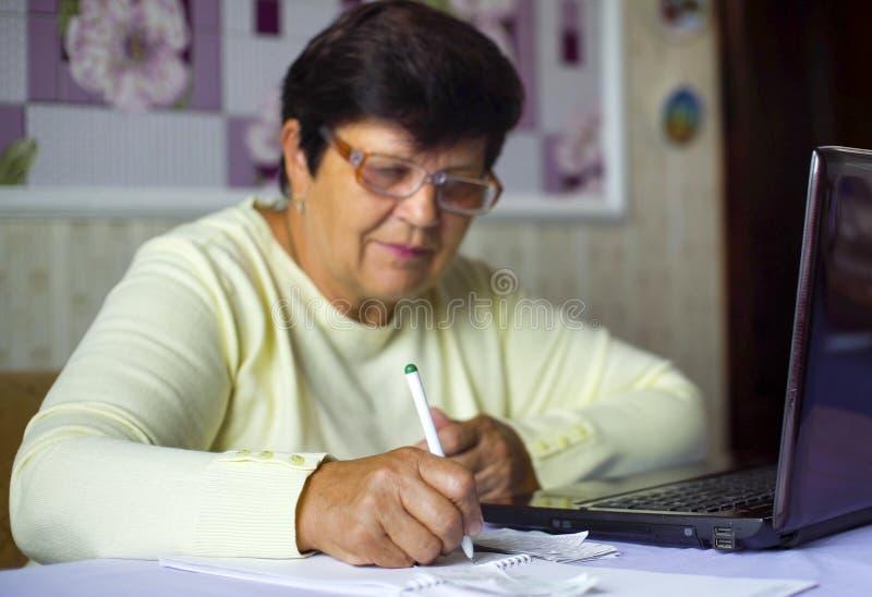 Ältere alte Frau in den Brillen Kosten der täglichen Ausgaben auf Laptop zu Hause überprüfend stockfoto