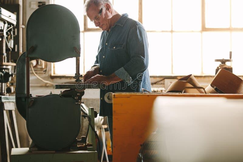 Ältere Arbeitskraft, die an Bandsägemaschine arbeitet lizenzfreies stockfoto