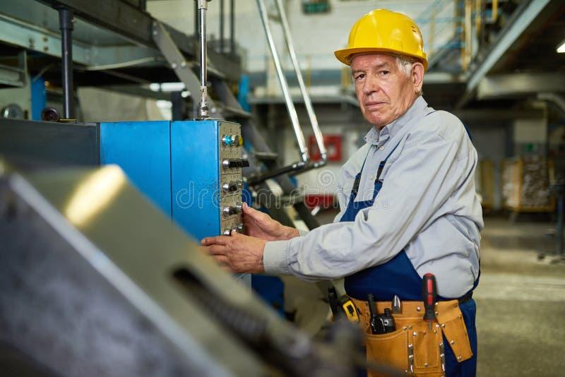 Ältere Arbeitskraft-funktionierende Maschineneinheiten an der Fabrik lizenzfreie stockbilder