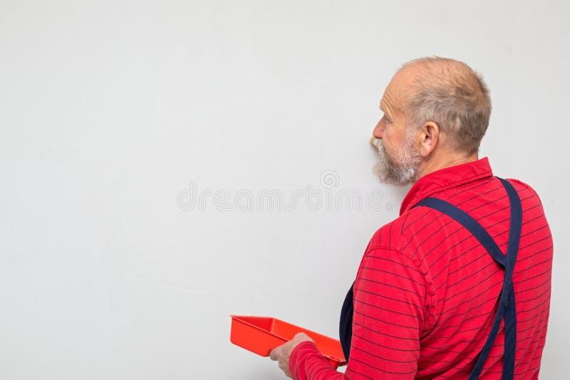 Ältere Arbeitskraft, welche die Wände malt lizenzfreie stockbilder