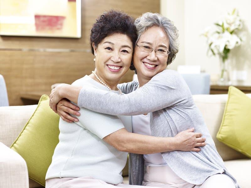 Ältere asiatische Frauen, die sich umarmen stockfotografie