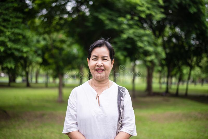 Ältere asiatische Frauenstellung und Kamera Park-, glücklichem und Lächelngesicht betrachten stockbild