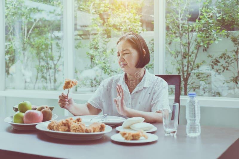 Ältere asiatische glaubende Frau unglückliche und gebohrte Mahlzeit, älteres gesundes Konzept lizenzfreies stockbild
