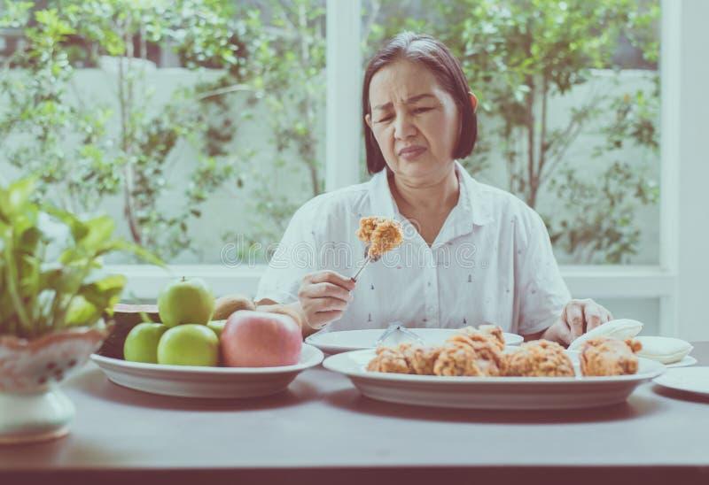 Ältere asiatische glaubende Frau unglückliche und gebohrte Mahlzeit, älteres gesundes Konzept stockfotografie