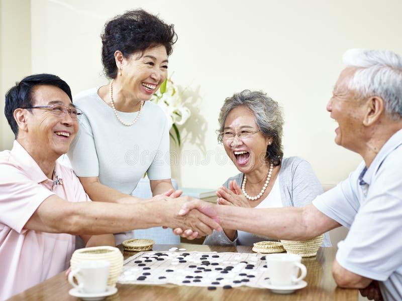 Ältere asiatische Leute, die weiqi spielen stockfoto