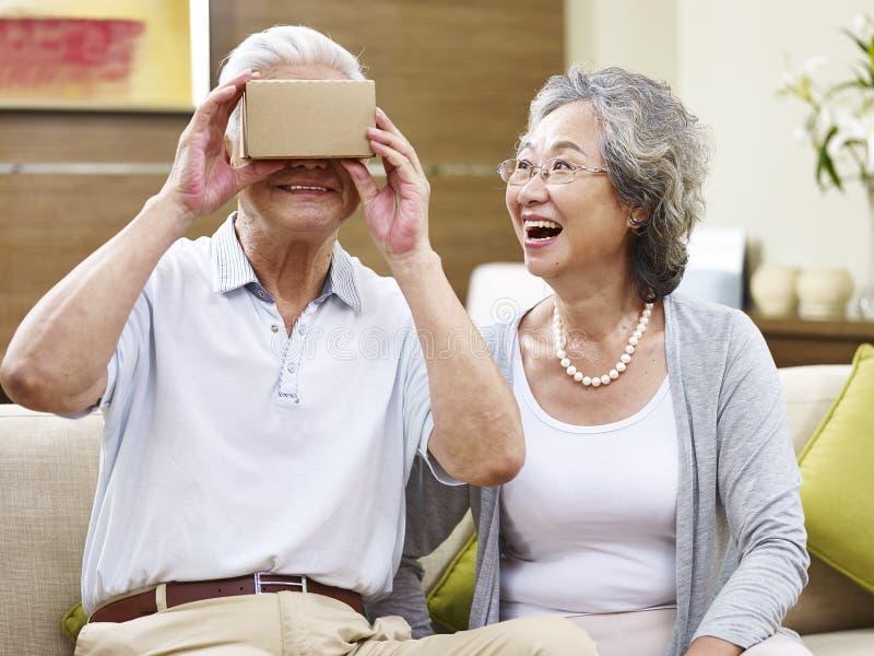 Ältere asiatische Leute versuchendes vr Gerät stockbild