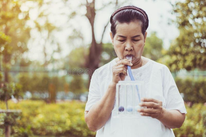 Ältere asiatische Mutter, die ein Incentive-Spirometer oder drei Kugeln zur Stimulierung der Lunge in der Natur verwendet lizenzfreie stockfotos
