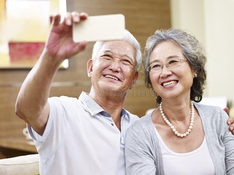 Ältere asiatische Paare, die ein selfie nehmen stockfotografie
