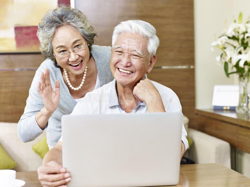 Ältere asiatische Paare, die online plaudern stockfoto