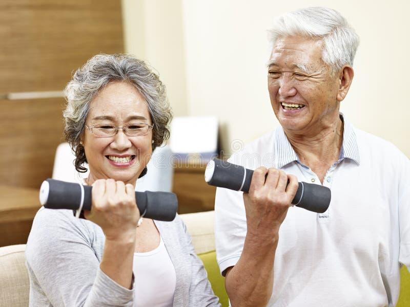 Ältere asiatische Paare, die unter Verwendung der Dummköpfe trainieren stockbilder