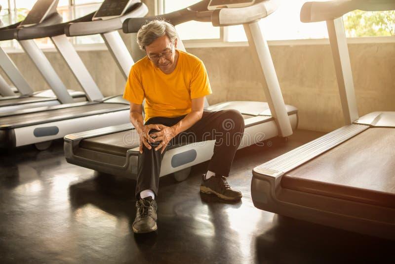 Ältere asiatische Sportmannverletzungs-Knieschmerz, die auf Tretmühle in der Eignungsturnhalle sitzen gealtertes Leiden vom älter stockfotos