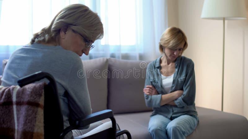Ältere behinderte Mutter, die mit umgekippter Tochter, Familienprobleme, Streit spricht lizenzfreie stockbilder