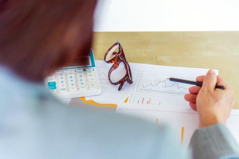 ältere berufstätige Frau, die Bleistift mit Brillen, Taschenrechner hält stockfoto