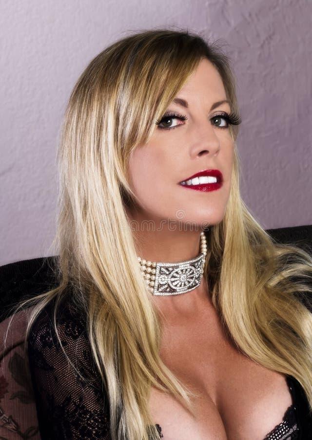Ältere blonde Frau im Spitzenoberteil mit dem Halsketten-Lächeln lizenzfreies stockfoto