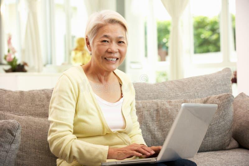 Ältere chinesische Frau, die Laptop verwendet, während entspannend stockfotos