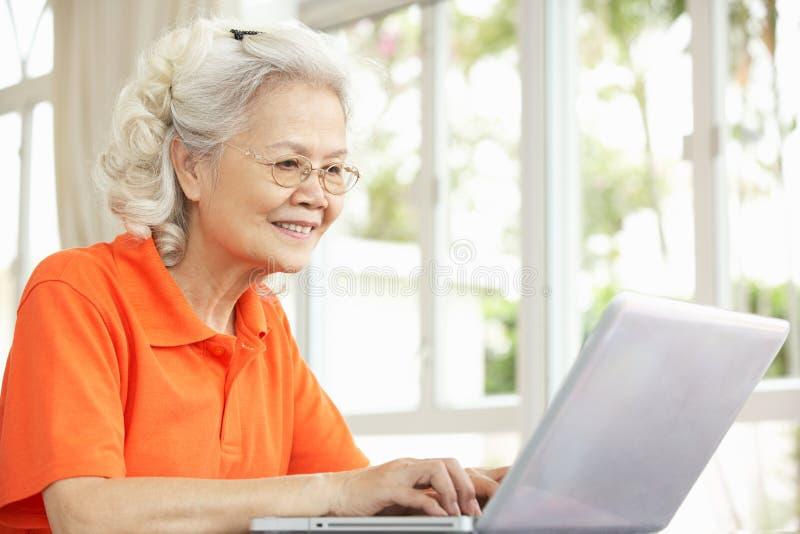 Ältere chinesische Frau, die zu Hause Laptop verwendet stockfotografie