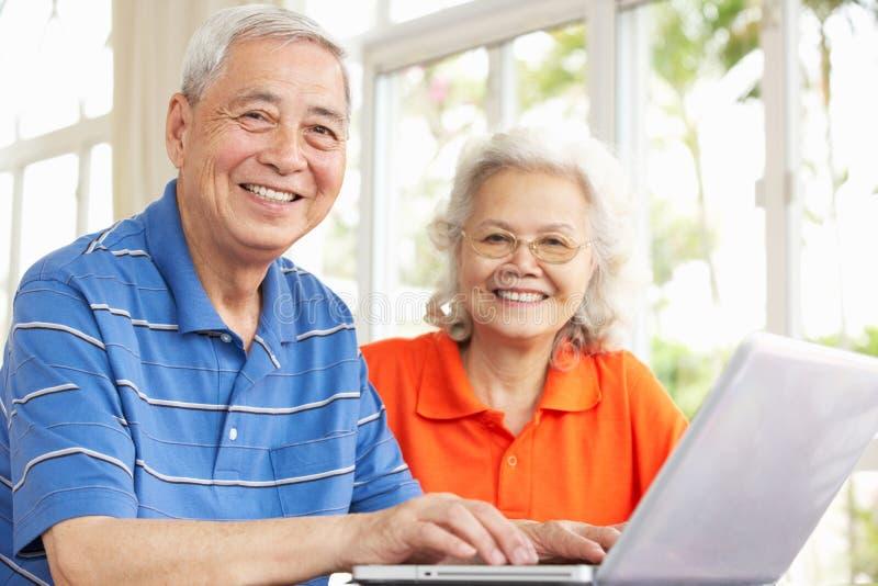 Ältere chinesische Paare unter Verwendung des Laptops zu Hause stockfoto