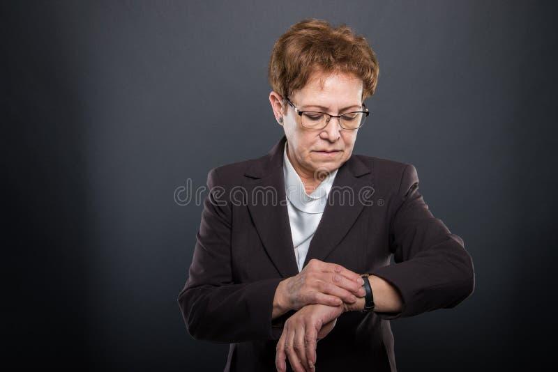 Ältere Dame des Geschäfts, die ihre Armbanduhr überprüft lizenzfreie stockfotografie
