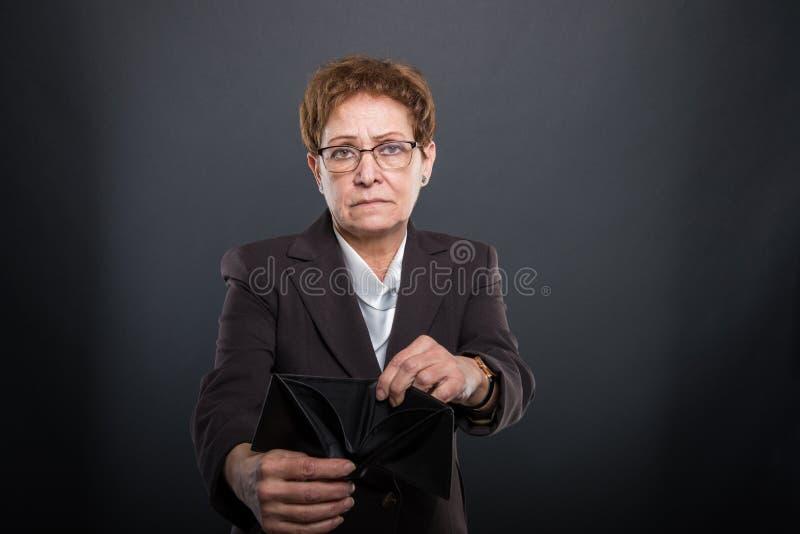 Ältere Dame des Geschäfts, die leere Geldbörse zeigt lizenzfreies stockbild