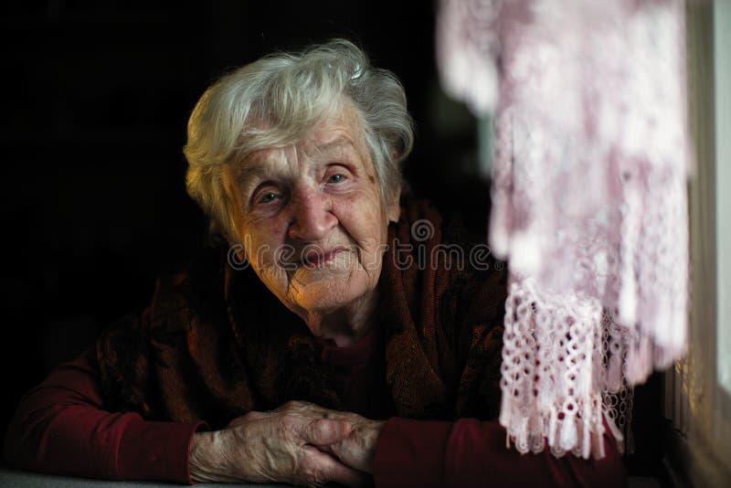 Ältere Dame, die in der Dunkelheit im Haus sitzt stockfotografie