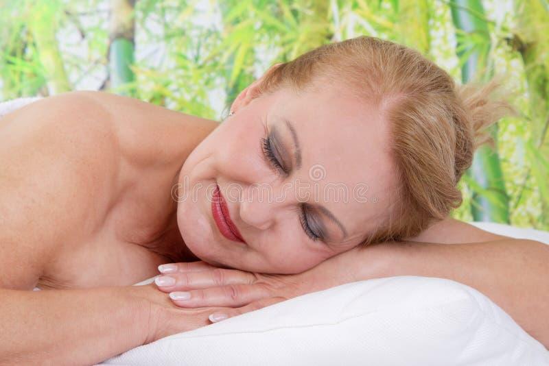 Ältere Dame, die in der Massage sich entspannt stockbilder