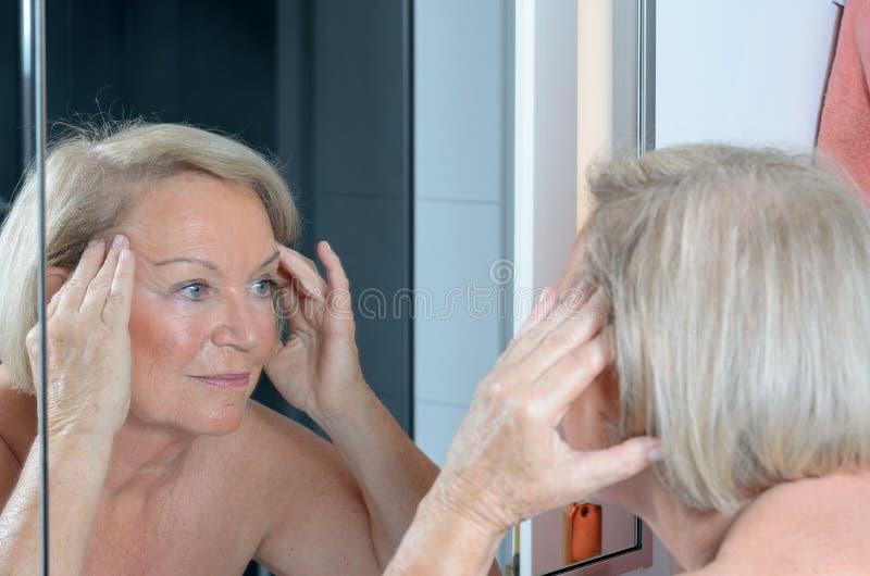 Ältere Dame, die ihre Haut im Spiegel überprüft lizenzfreies stockfoto