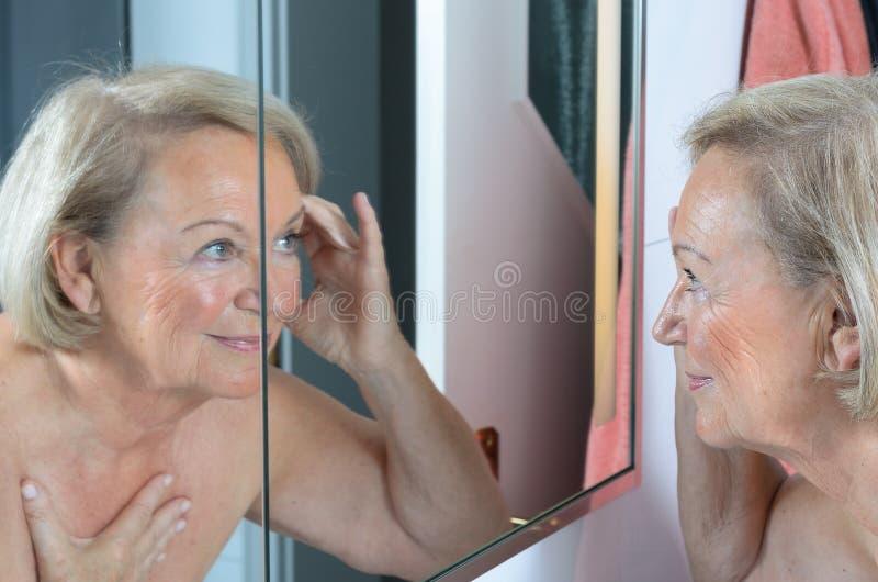 Ältere Dame, die ihre Haut im Spiegel überprüft stockbild