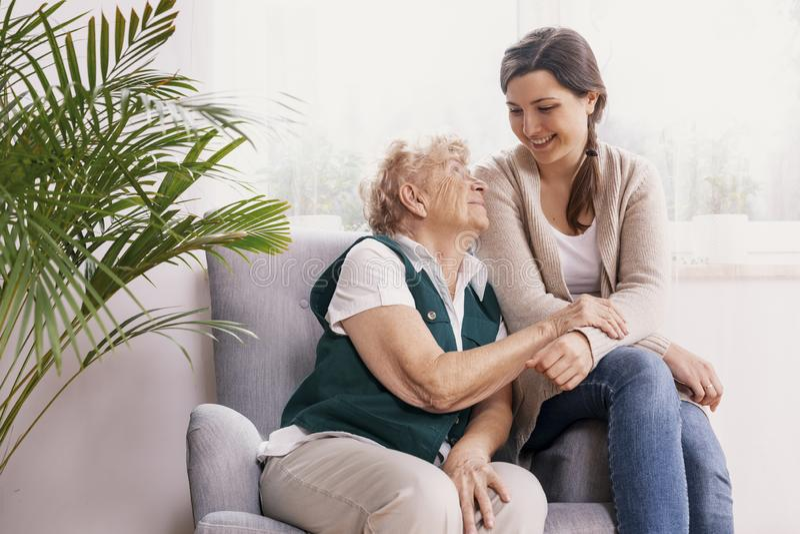 Ältere Dame, die im Lehnsessel am Pflegeheim, Unterstützungskrankenschwester sitzt stockbild