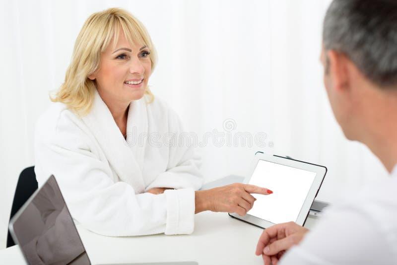Ältere Dame, die um Rat im talentierten Kosmetiker bittet stockfoto