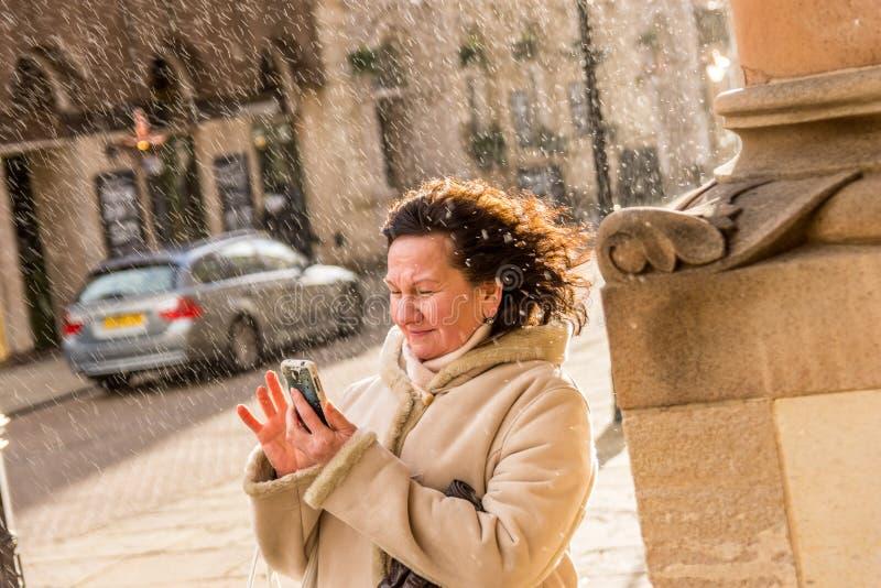 Ältere Dame, die versucht, Foto in regnerischem England zu machen stockfoto