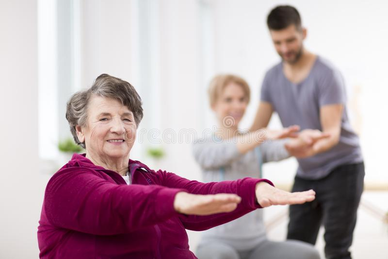 Ältere Dame, die während der Gruppenphysiotherapie in Rehabilitationszentrum trainiert lizenzfreie stockfotografie