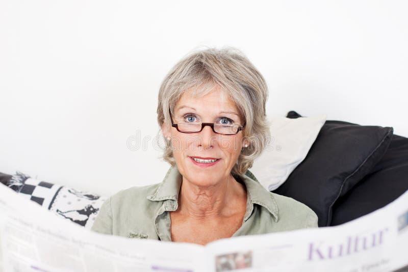 Ältere Dame, die zu Hause ihre Zeitung liest stockfoto