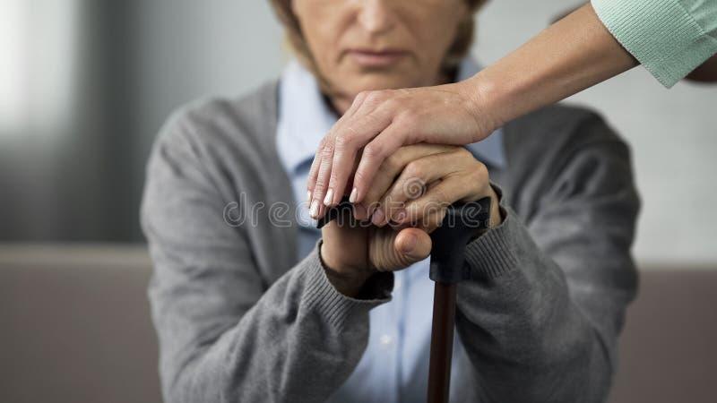 Ältere Dame im Ruhestand, die auf Sofa, junge Frau sorgfältig berührt ihre Hände sitzt stockfotografie