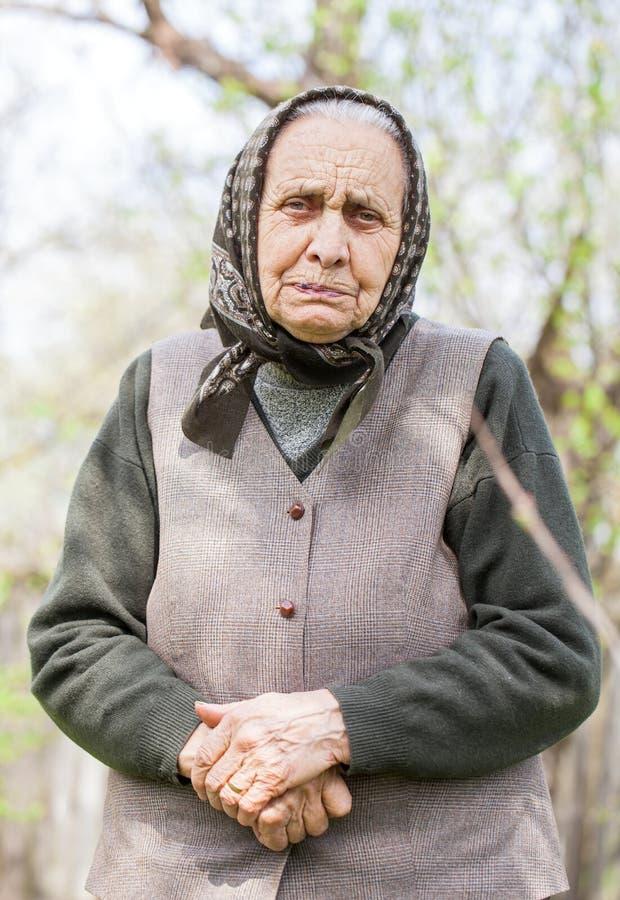 Ältere Dame mit dem Kopftuch im Freien stockbilder