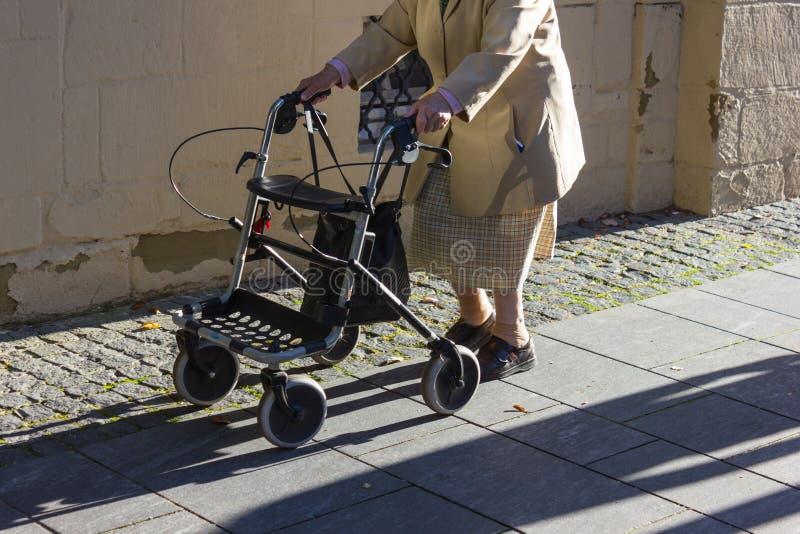 ältere Dame mit rollator gehend in ein deutsches historisches Südc stockbild