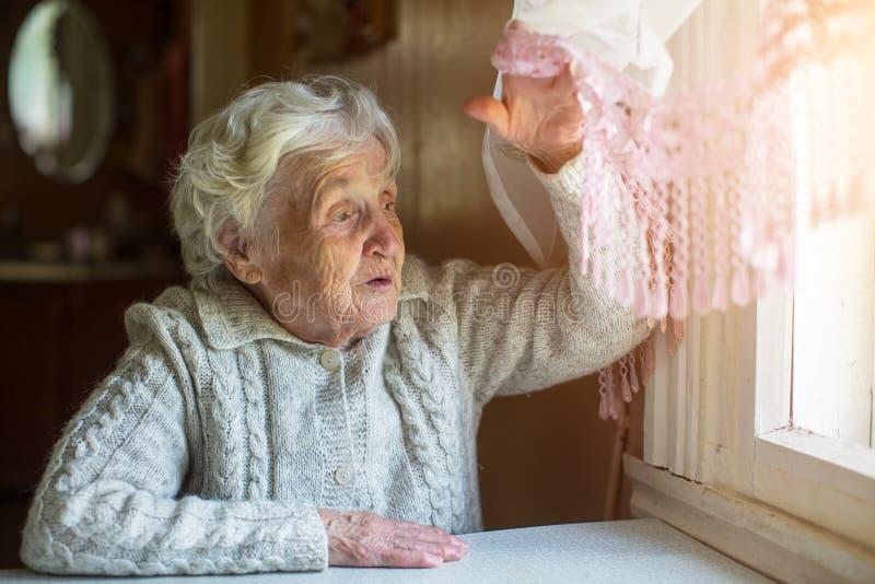 Ältere Dame schaut aus dem Fenster heraus lizenzfreies stockbild