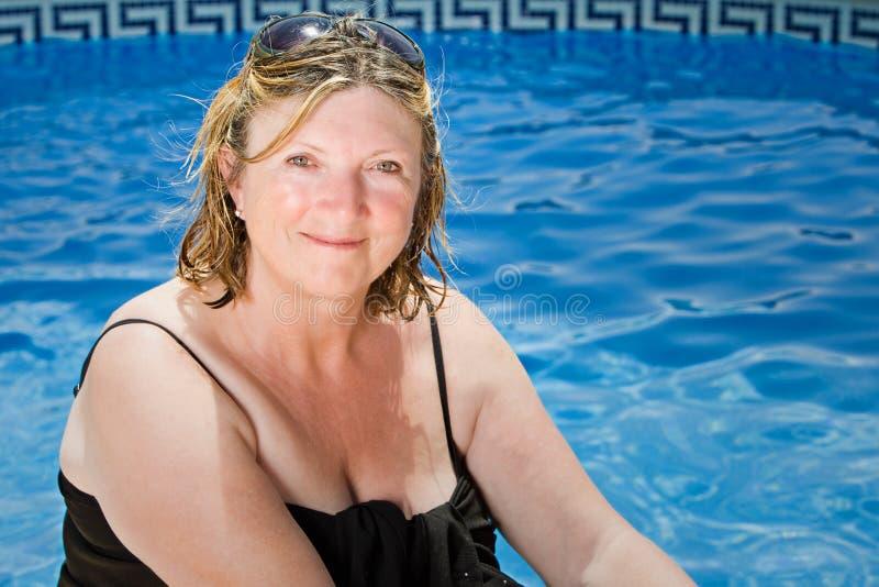 Ältere Dame Sitting durch das Pool lizenzfreies stockfoto