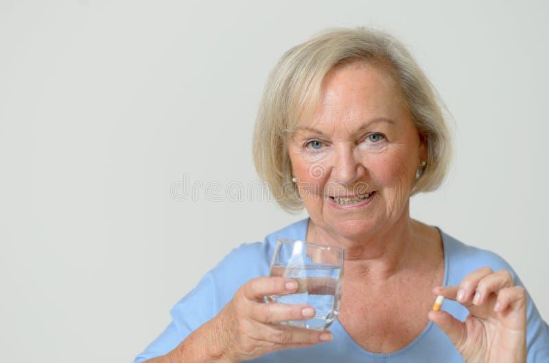 Ältere Dame, welche die vorgeschriebene Dosis von Medizin nimmt stockfotografie