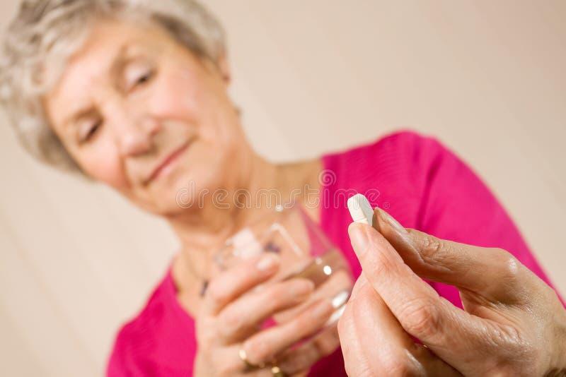 Ältere Dameholdingtablette oder -pille mit Wasser stockbilder