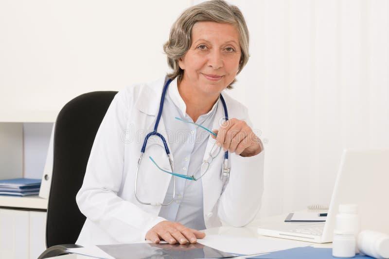 Ältere Doktorfrau sitzen hinter Büroschreibtisch lizenzfreies stockbild