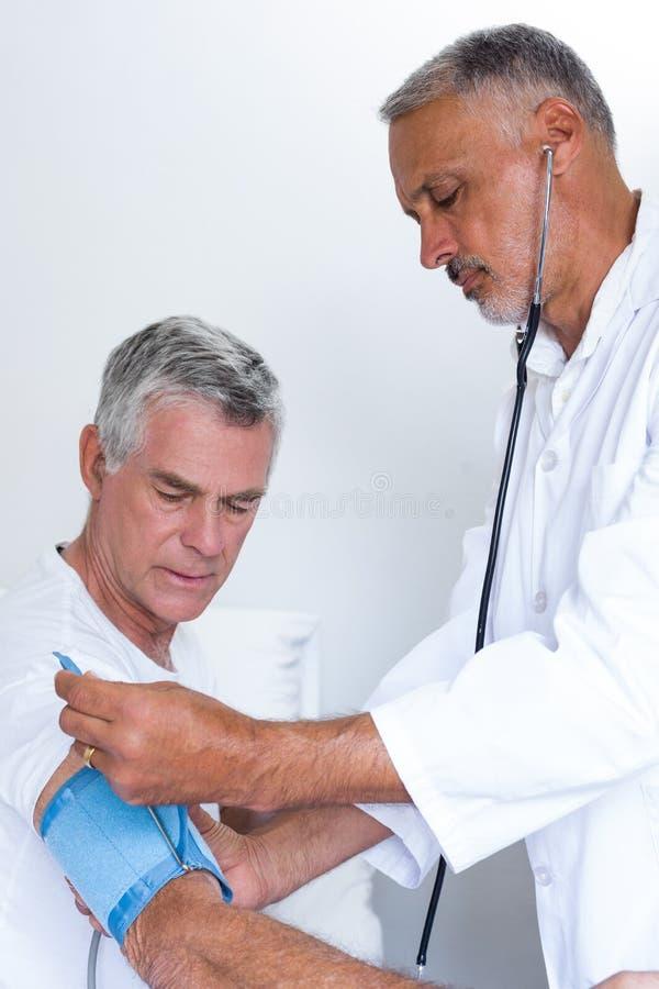 Ältere Doktorprüfung bemannt Blutdruck stockfoto