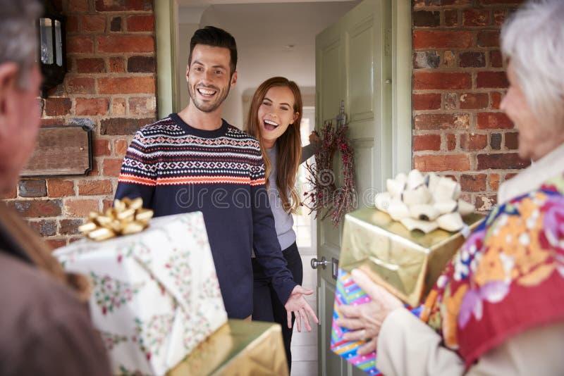 Ältere Eltern, die von der erwachsenen Nachkommenschaft gegrüßt werden, wie sie für Besuch am Weihnachtstag ankommen lizenzfreie stockbilder