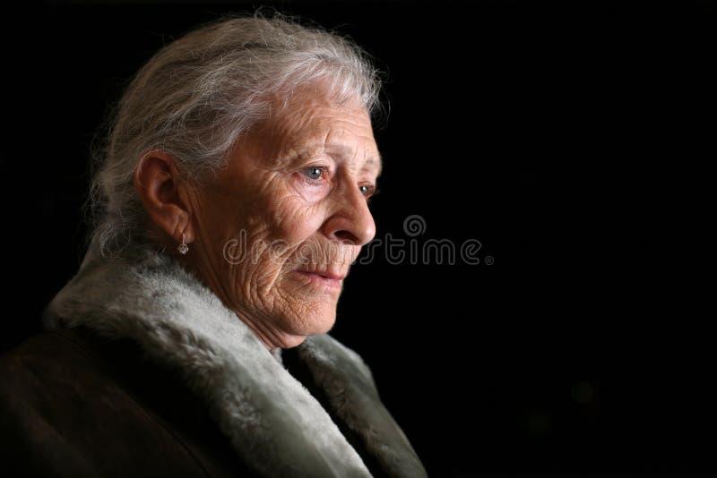 Ältere erwägende Frau stockbild