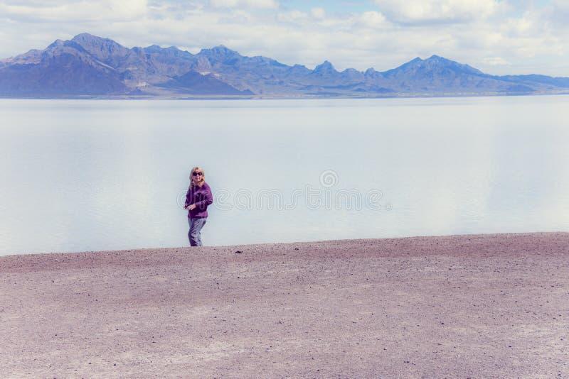 Ältere erwachsene Frau steht im flachen Bonneville-Salz, wenn es an einem Sommertag überschwemmt wird stockbild