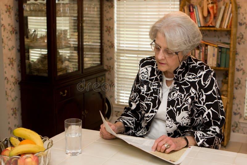 Ältere erwachsene Frauen-Lesezeitschrift lizenzfreie stockfotos